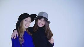Δύο νέα κορίτσια στο καπέλο που χορεύει και που θέτει στη κάμερα στο υπόβαθρο απόθεμα βίντεο