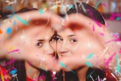 Δύο νέα λεσβιακά κορίτσια κάνουν μια καρδιά με τα χέρια τους σε ένα κόμμα λεσχών στοκ φωτογραφίες με δικαίωμα ελεύθερης χρήσης