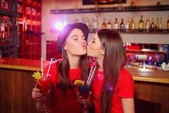 Δύο νέα λεσβιακά κορίτσια που φιλούν σε ένα κόμμα λεσχών στοκ εικόνες