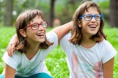 Δύο νέα με ειδικές ανάγκες παιδιά που γελούν υπαίθρια. στοκ εικόνες