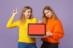 Δύο νέα ξανθά κορίτσια αδελφών διδύμων που δείχνουν το δάχτυλο επάνω, υπολογιστής PC lap-top λαβής με την κενή κενή οθόνη επάνω στοκ φωτογραφία