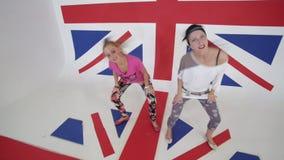 Δύο νέα χαμογελώντας θηλυκά στις μπλούζες εξετάζουν τη κάμερα και συγχρονικά το χορό φιλμ μικρού μήκους