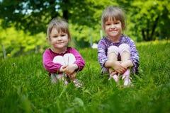 Δύο νέα χαμογελώντας κορίτσια στη χλόη στοκ φωτογραφίες με δικαίωμα ελεύθερης χρήσης