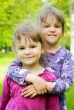Δύο νέα χαμογελώντας κορίτσια στη χλόη στοκ εικόνες