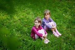 Δύο νέα χαμογελώντας κορίτσια στη χλόη στοκ εικόνα με δικαίωμα ελεύθερης χρήσης