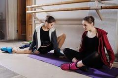 Δύο νέα χαριτωμένα ballerinas κάνουν το τέντωμα πρίν εκπαιδεύουν ή την πρόβα στοκ εικόνες
