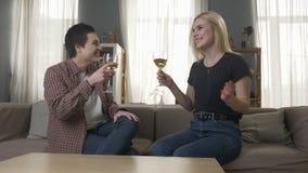 Δύο νέα, όμορφα κορίτσια κάθονται στον καναπέ, αυξάνουν τα γυαλιά με το κρασί και, λεσβίες, LGBT, ξανθό φιλμ μικρού μήκους