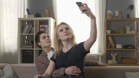 Δύο νέα, όμορφα κορίτσια κάθονται στον καναπέ και κάνουν selfies, λεσβίες, LGBT, ξανθό, brunette 60 fps φιλμ μικρού μήκους