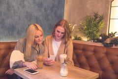 Δύο νέα όμορφα κορίτσια που κάθονται στον καφέ, πίνουν τον καφέ και usin στοκ φωτογραφίες