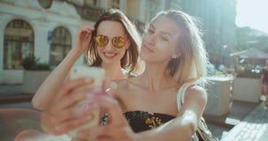 Δύο νέα όμορφα κορίτσια που παίρνουν selfie σε μια οδό πόλεων