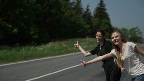 Δύο νέα hitchhikers γυναικών στέκονται στα περιθώρια και ζητούν να σταματήσουν τα περνώντας αυτοκίνητα απόθεμα βίντεο