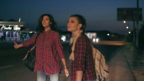 Δύο νέα hitchhikers γυναικών στέκονται στα περιθώρια που κρατούν τα σακίδια πλάτης τους και ζητούν να σταματήσουν τα περνώντας αυ απόθεμα βίντεο