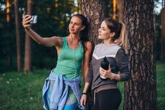 Δύο νέες αθλητικές φίλες που φορούν sportswear που κλίνει ενάντια στο δέντρο που παίρνει selfie με το smartphone στο δάσος στοκ φωτογραφίες με δικαίωμα ελεύθερης χρήσης