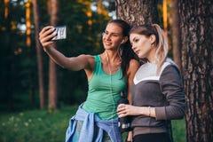 Δύο νέες αθλητικές φίλες που φορούν sportswear που κλίνει ενάντια στο δέντρο που παίρνει selfie με το smartphone στο δάσος στοκ φωτογραφία με δικαίωμα ελεύθερης χρήσης