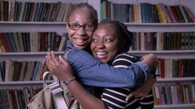 Δύο νέες γυναίκες αφροαμερικάνων που αγκαλιάζουν στη βιβλιοθήκη και που εξετάζουν τη κάμερα, ευτυχής και εύθυμος φιλμ μικρού μήκους