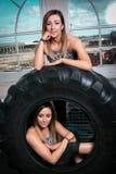 Δύο νέες γυναίκες ικανότητας που στηρίζονται σε ένα ελαστικό αυτοκινήτου Στοκ εικόνες με δικαίωμα ελεύθερης χρήσης