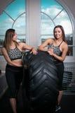 Δύο νέες γυναίκες ικανότητας που στηρίζονται σε ένα ελαστικό αυτοκινήτου Στοκ Εικόνες