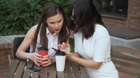 Δύο νέες γυναίκες κάθονται σε έναν πίνακα σε έναν θερινό καφέ και κουβεντιάζουν χαρούμενα το κορίτσι παρουσιάζει στο φίλο της κάτ απόθεμα βίντεο
