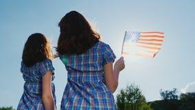 Δύο νέες γυναίκες με τη αμερικανική σημαία Στις ακτίνες του ήλιου ενάντια στον ουρανό απομονωμένο οπισθοσκόπο λευκό ανεξαρτησία η απόθεμα βίντεο
