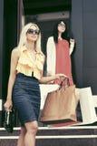 Δύο νέες γυναίκες μόδας με τις τσάντες αγορών στην πόρτα λεωφόρων Στοκ Εικόνα