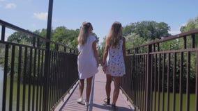 Δύο νέες γυναίκες περπατούν στη μικρή γέφυρα στο πάρκο απόθεμα βίντεο