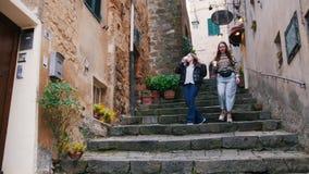 Δύο νέες γυναίκες πηγαίνουν κάτω από τα σκαλοπάτια με τα φλυτζάνια στα χέρια τους απόθεμα βίντεο