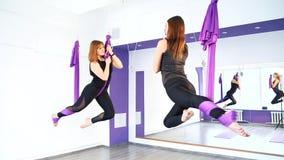 Δύο νέες γυναίκες που ασκούν τη γιόγκα στις αιώρες στο στούντιο απόθεμα βίντεο