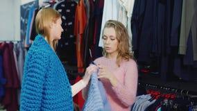 Δύο νέες γυναίκες που επιλέγουν τα ενδύματα σε ένα κατάστημα Επικοινωνήστε, εξετάζοντας τις μελλοντικές αγορές απόθεμα βίντεο