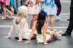 Δύο νέες γυναίκες που κάθονται στο πεζοδρόμιο στο σταθμό οδών Flinder στη Μελβούρνη Στοκ Εικόνες
