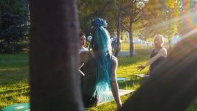 Δύο νέες γυναίκες που κάνουν τις διαφορετικές ασκήσεις γιόγκας με το λεωφορείο στο πάρκο - μια γυναίκα έχει τα μακροχρόνια μπλε d φιλμ μικρού μήκους
