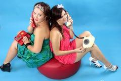 Δύο νέες γυναίκες που καλούν τα τηλέφωνα στο μπλε υπόβαθρο Στοκ Φωτογραφία