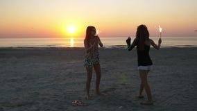 Δύο νέες γυναίκες που με τα κεριά πυροτεχνημάτων στην παραλία στην ανατολή απόθεμα βίντεο