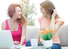 Δύο νέες γυναίκες που μιλούν και που κάθονται στο τραπεζάκι σαλονιού Στοκ Φωτογραφία