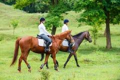 Δύο νέες γυναίκες που οδηγούν το άλογο στο πάρκο Στοκ εικόνες με δικαίωμα ελεύθερης χρήσης