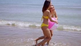 Δύο νέες γυναίκες που παίζουν με μια σφαίρα παραλιών φιλμ μικρού μήκους