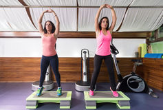 Δύο νέες γυναίκες που τεντώνουν stepper τη γυμναστική Στοκ φωτογραφία με δικαίωμα ελεύθερης χρήσης