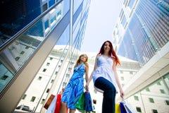 Δύο νέες γυναίκες που φέρνουν τις τσάντες αγορών Στοκ Φωτογραφία