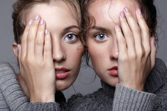 Δύο νέες γυναίκες στα γκρίζα πουλόβερ στο γκρίζο υπόβαθρο όμορφο γ Στοκ Φωτογραφίες
