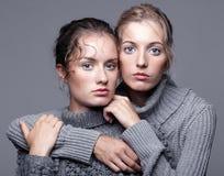 Δύο νέες γυναίκες στα γκρίζα πουλόβερ στο γκρίζο υπόβαθρο όμορφο γ Στοκ εικόνα με δικαίωμα ελεύθερης χρήσης