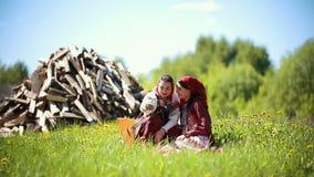 Δύο νέες γυναίκες στα παραδοσιακά ρωσικά ενδύματα που κάθονται στον τομέα και που παίρνουν ένα selfie φιλμ μικρού μήκους
