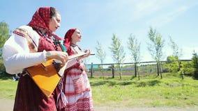 Δύο νέες γυναίκες στα παραδοσιακά ρωσικά ενδύματα που περπατούν στο δρόμο στο χωριό απόθεμα βίντεο