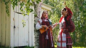 Δύο νέες γυναίκες στα παραδοσιακά ρωσικά ενδύματα που στέκονται κοντά σε ένα ξύλινο κτήριο έναν από τους παίζουν το balalaika φιλμ μικρού μήκους