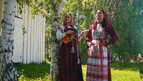 Δύο νέες γυναίκες στα ρωσικά φορέματα που στέκονται στο λιβάδι - μια από τις παιχνίδια το balalaika φιλμ μικρού μήκους