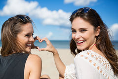 Δύο νέες γυναίκες στην παραλία που κατασκευάζουν την καρδιά να υπογράψει το γέλιο Στοκ Εικόνα