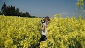 Δύο νέες γυναίκες στις μαύρες φόρμες ενδυμάτων που τρέχουν μέσω του κίτρινου τομέα σχετικά με τα λουλούδια HD φιλμ μικρού μήκους
