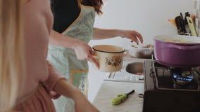 Δύο νέες γυναίκες στις ποδιές μαγειρεύουν στην κουζίνα Βάζουν στη σόμπα αερίου που πιατικά, βράζουν ένα καλαμάρι, κινηματογράφηση απόθεμα βίντεο