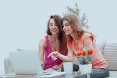 Δύο νέες γυναίκες συζητούν το βίντεο με τη συνεδρίαση lap-top σε ένα τραπεζάκι σαλονιού Στοκ Φωτογραφία