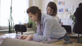 Δύο νέες γυναίκες σχεδιάζουν το ύφασμα στον πίνακα στο ράψιμο του εργαστηρίου, οι θηλυκοί επαγγελματίες συνεχίζουν εργασίας με το απόθεμα βίντεο