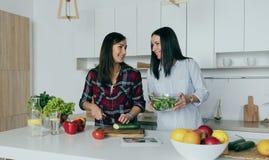 Δύο νέες εύθυμες φίλες που μαγειρεύουν την εγχώρια κουζίνα σαλάτας στοκ εικόνες