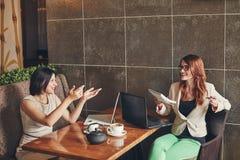 Δύο νέες καυκάσιες επιχειρηματίες με το lap-top, σημειωματάριο Γυναίκες στον καφέ Στοκ εικόνα με δικαίωμα ελεύθερης χρήσης
